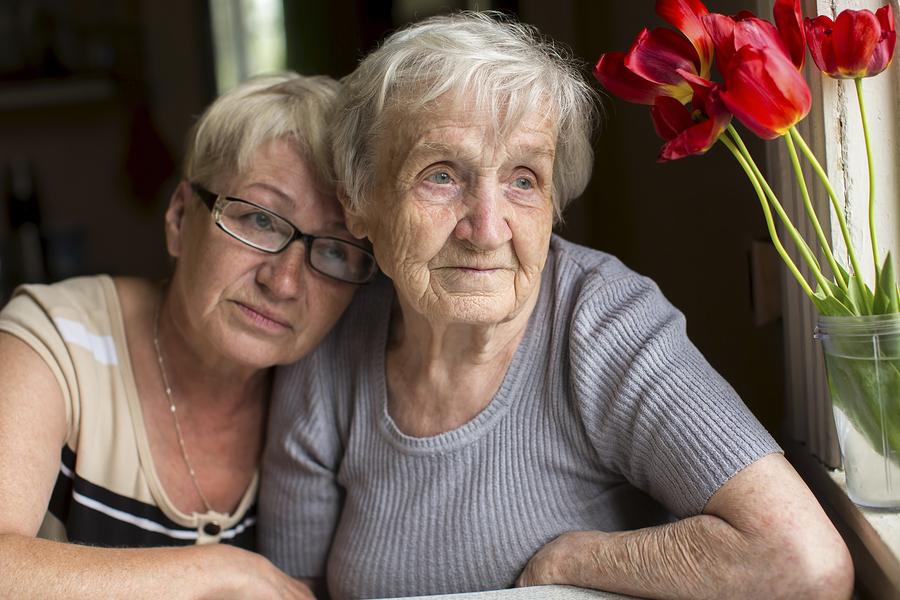 Elderly mom with her stressed, guilt-ridden caregiver daughter